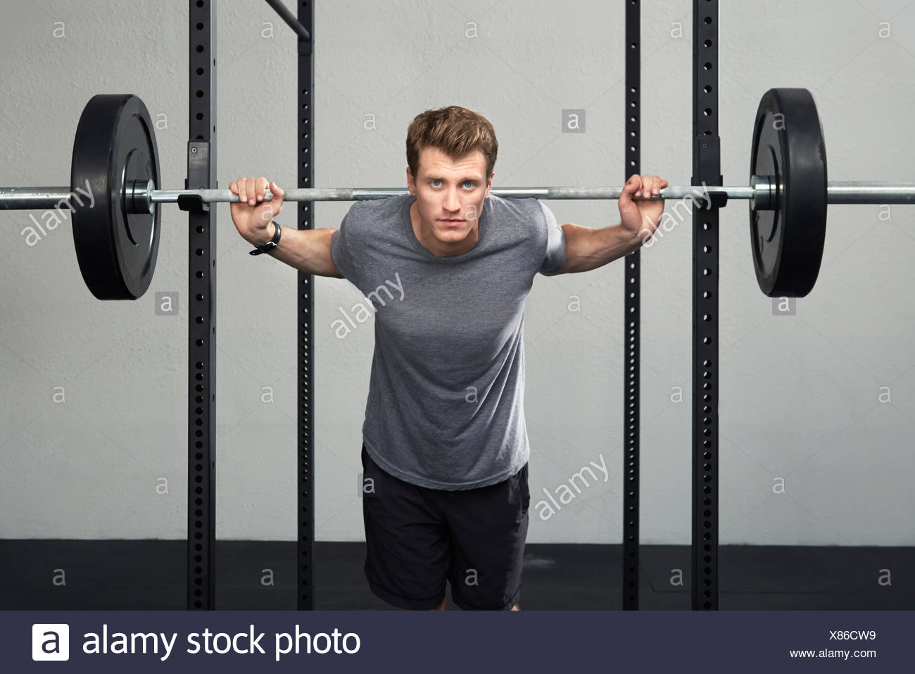 Portrait of mid adult male weightlifter lifting barbell in gym - Stock Image