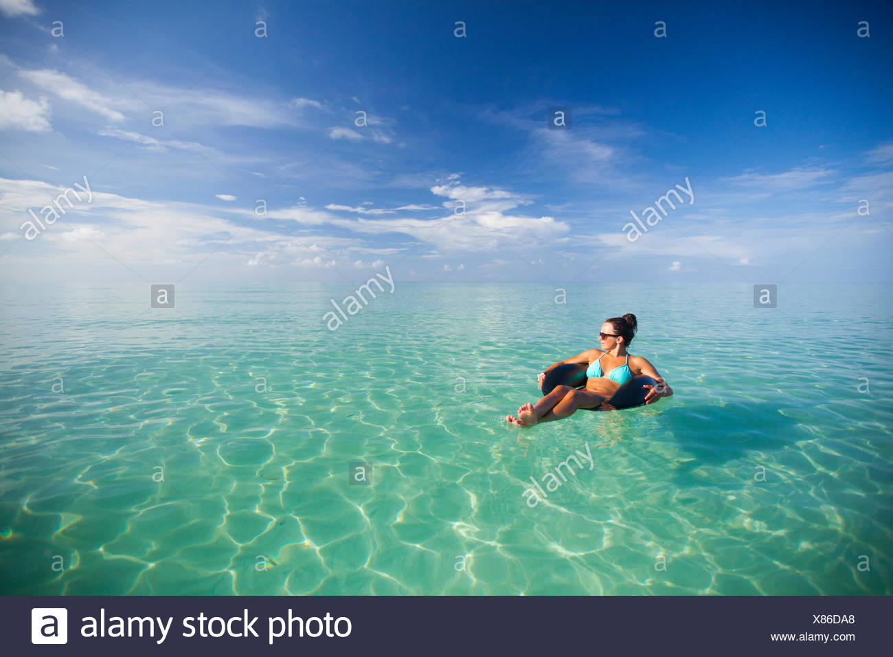 A young woman floats on an inflatable water toy in turquoise water. Stock Photo
