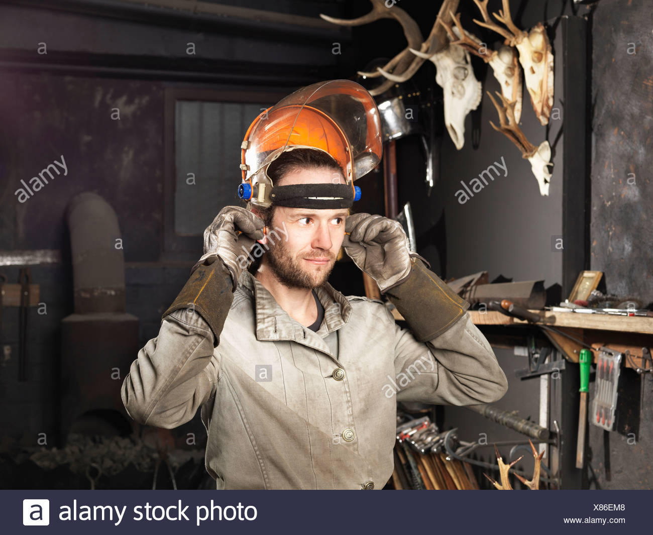 Blacksmith putting on a visor in workshop - Stock Image