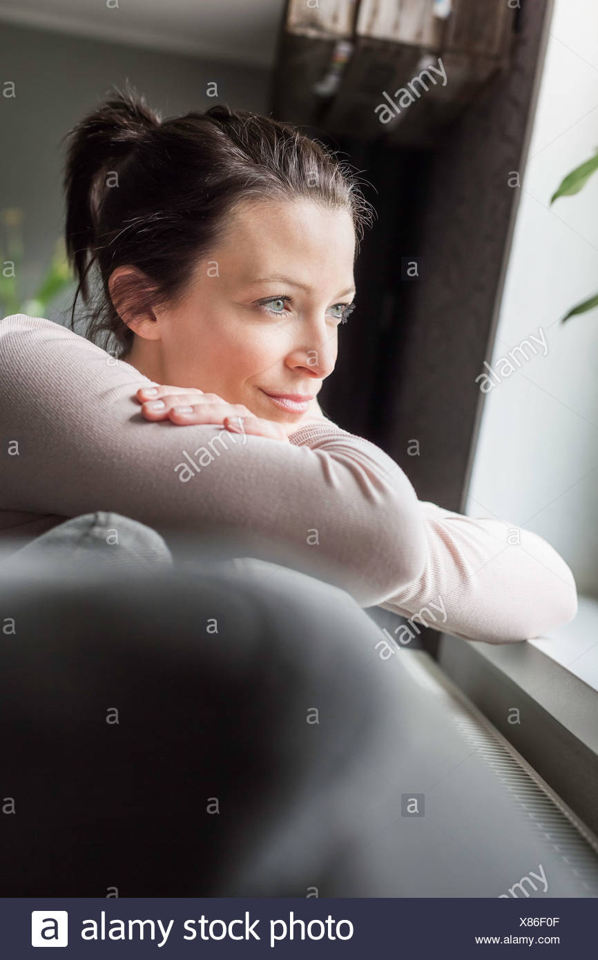 Mid adult woman looking out of window - Stock Image