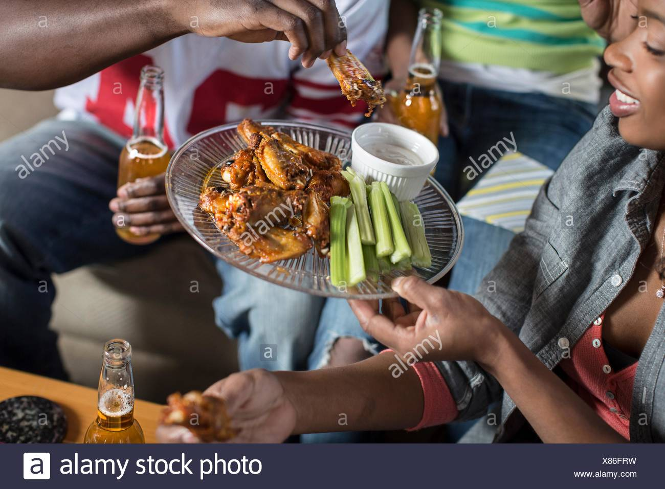 Group of adult friends sharing takeaway on living room sofa - Stock Image