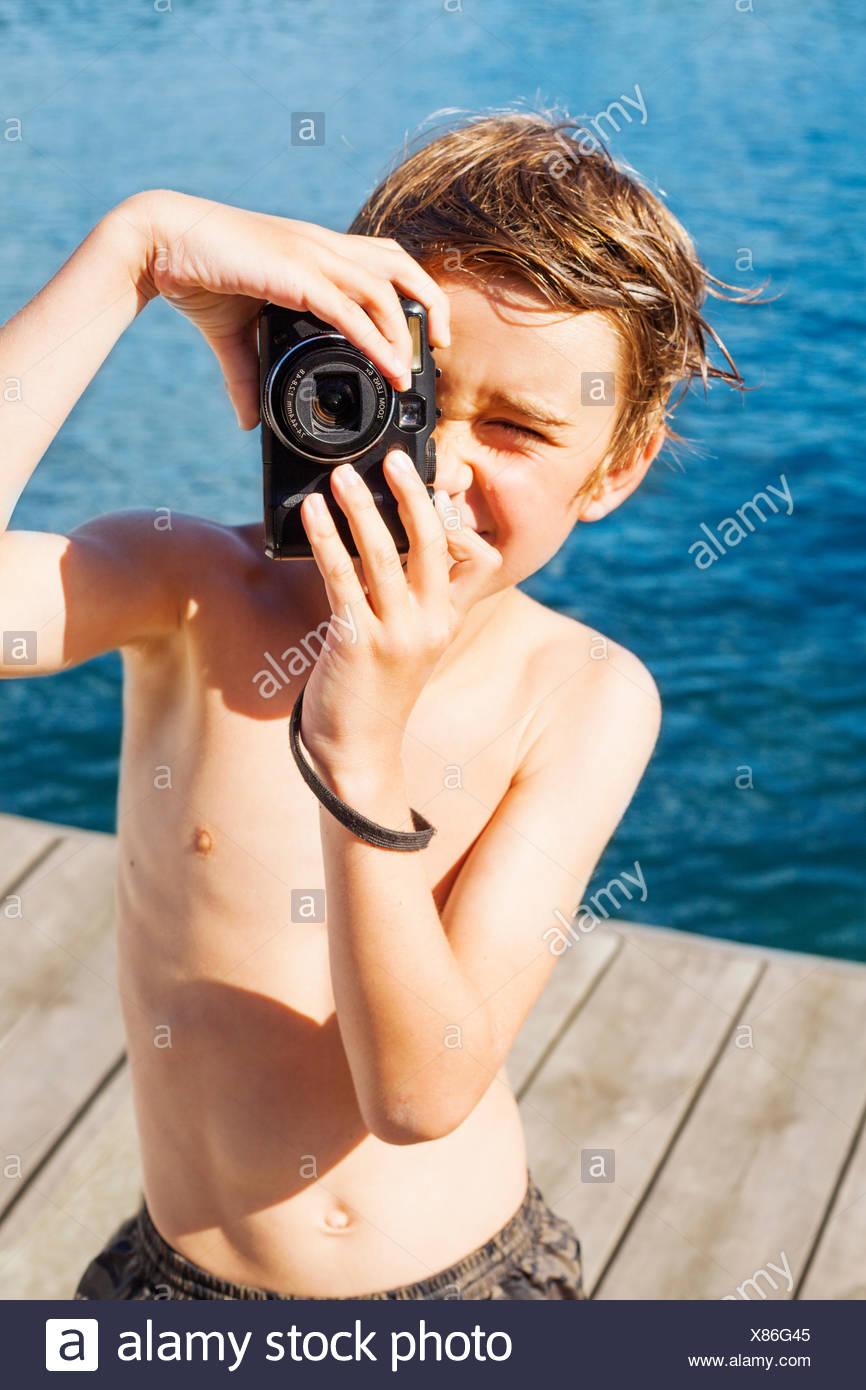 Sweden, Uppland, Runmaro, Barrskar, Portrait of boy (6-7) photographing on jetty - Stock Image
