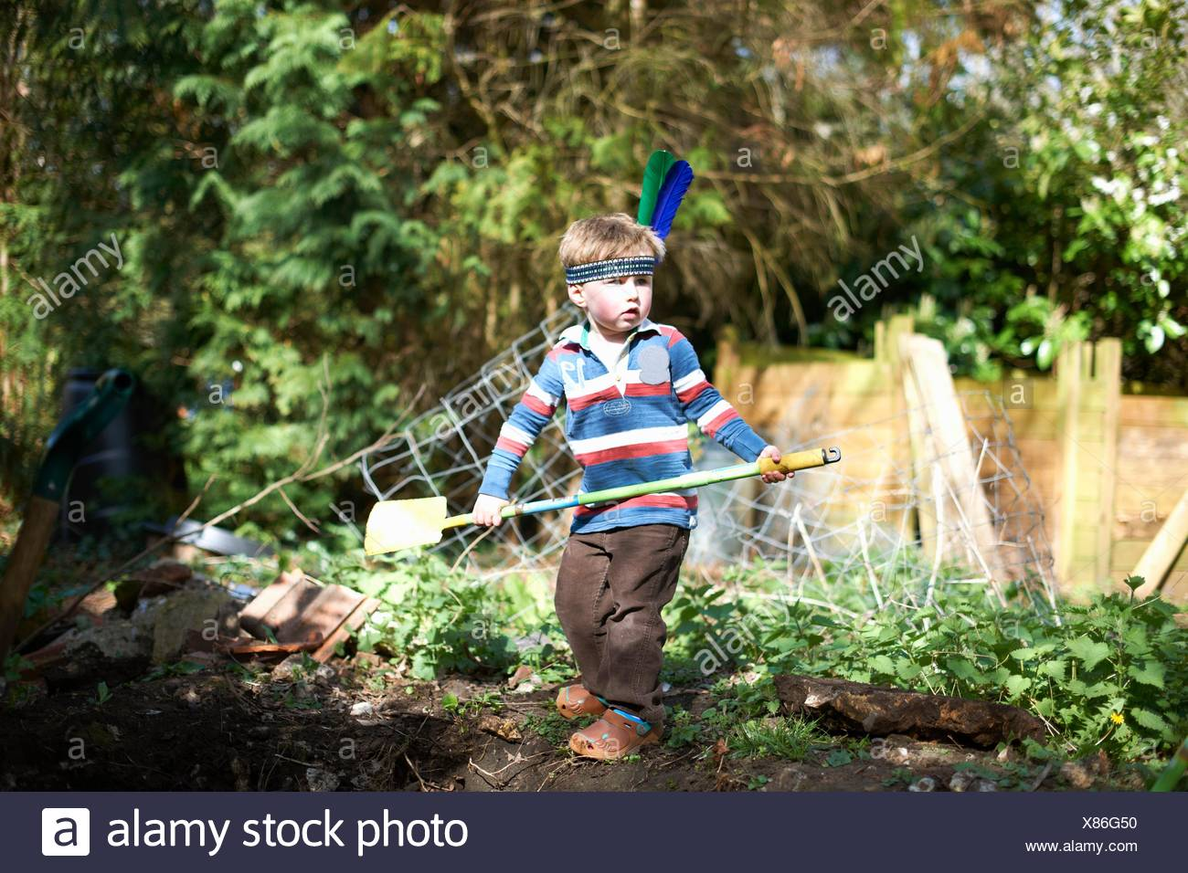 Young boy wearing headband with feathers, holding spade - Stock Image