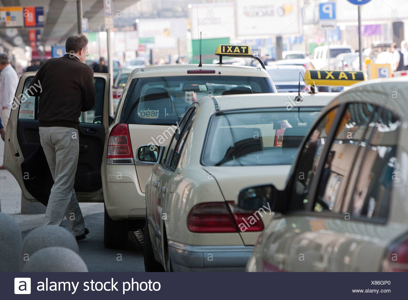 Passenger entering a waiting taxi, Frankfurt Airport, Hesse, Germany, Europe - Stock Image