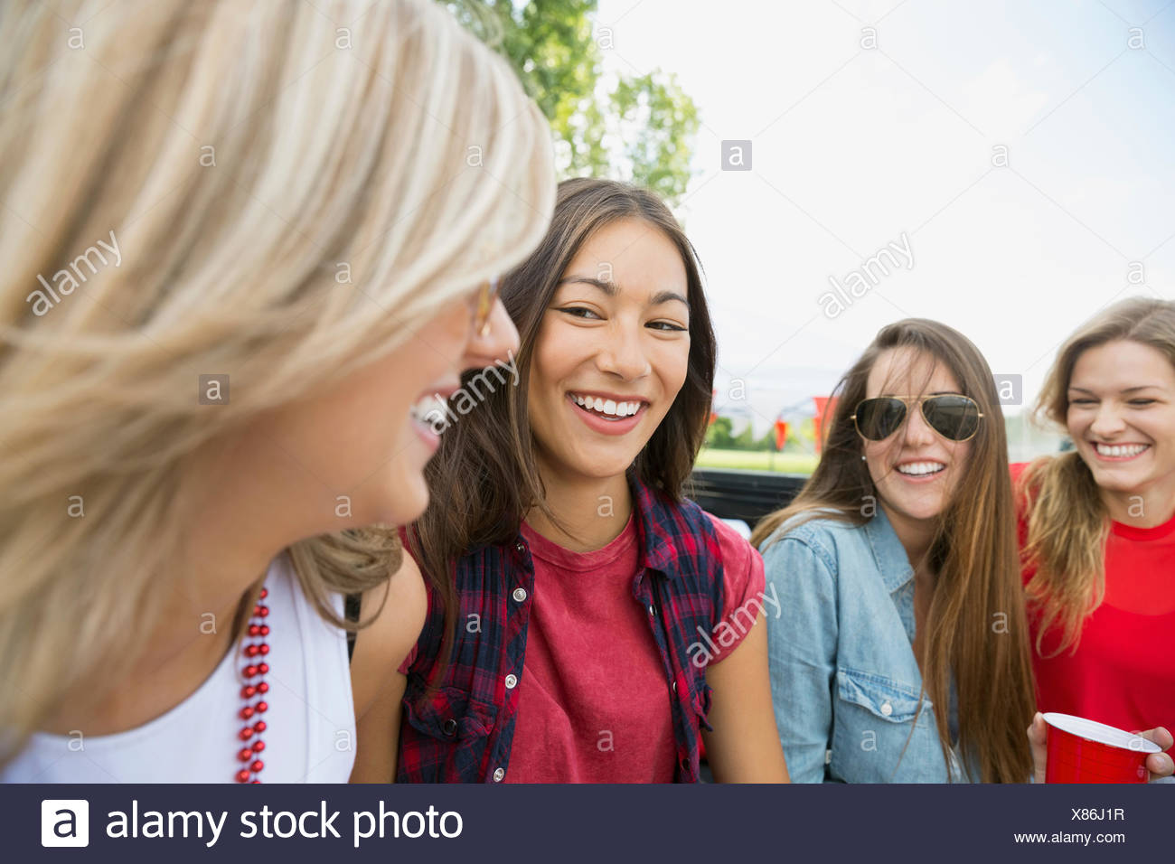 Women smiling together outdoors - Stock Image
