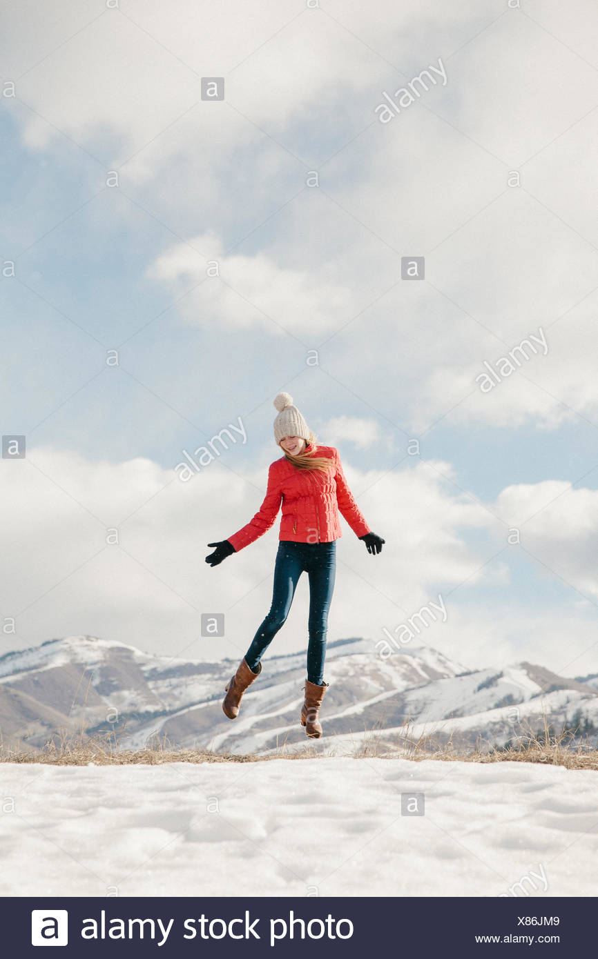 A young girl with long legs and red jacket, leaping in the air above the snow - Stock Image