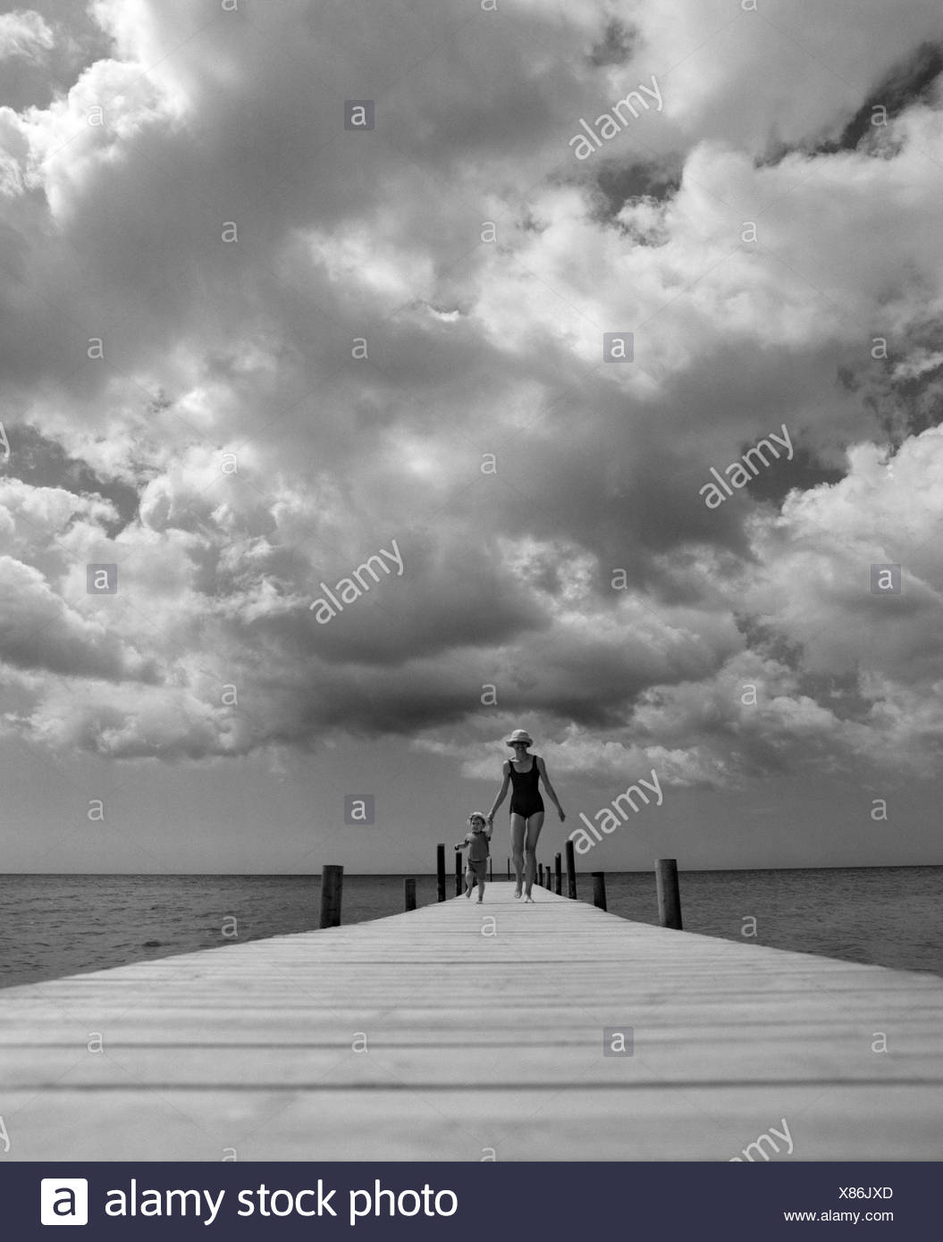 Mother and daughter running on a pier, Oland, Sweden. - Stock Image