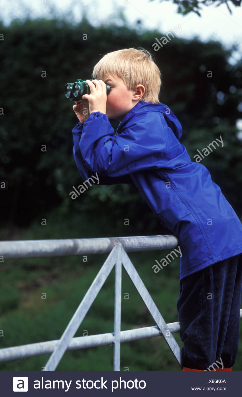 young school boy lookng through binoculars over a field gate - Stock Image