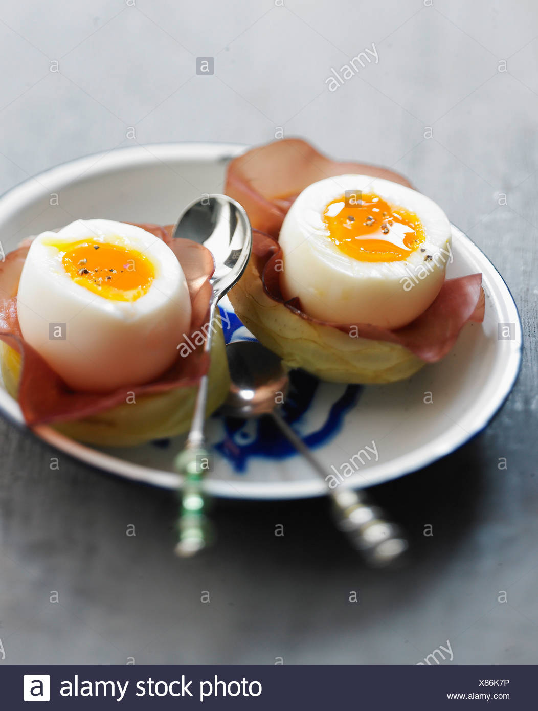 Soft-boiled eggs on artichoke bases with grisons meat - Stock Image