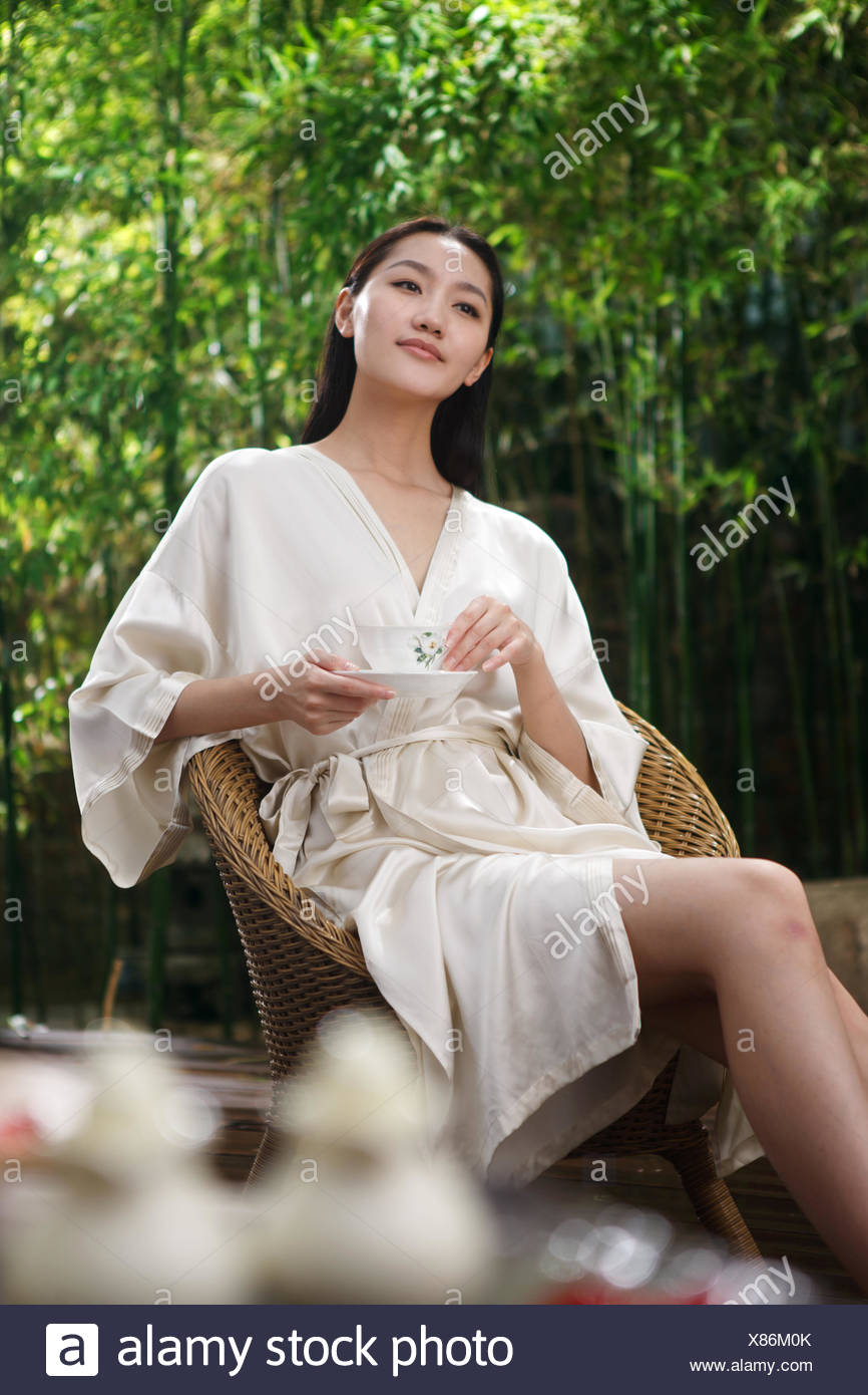 Robe young woman holding a Coffee cup - Stock Image