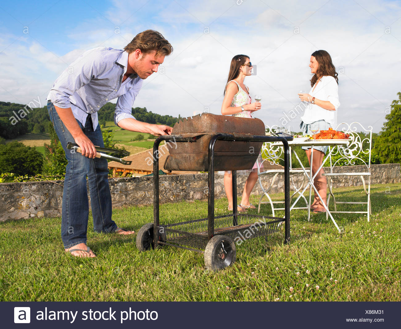 man tending barbecue - Stock Image