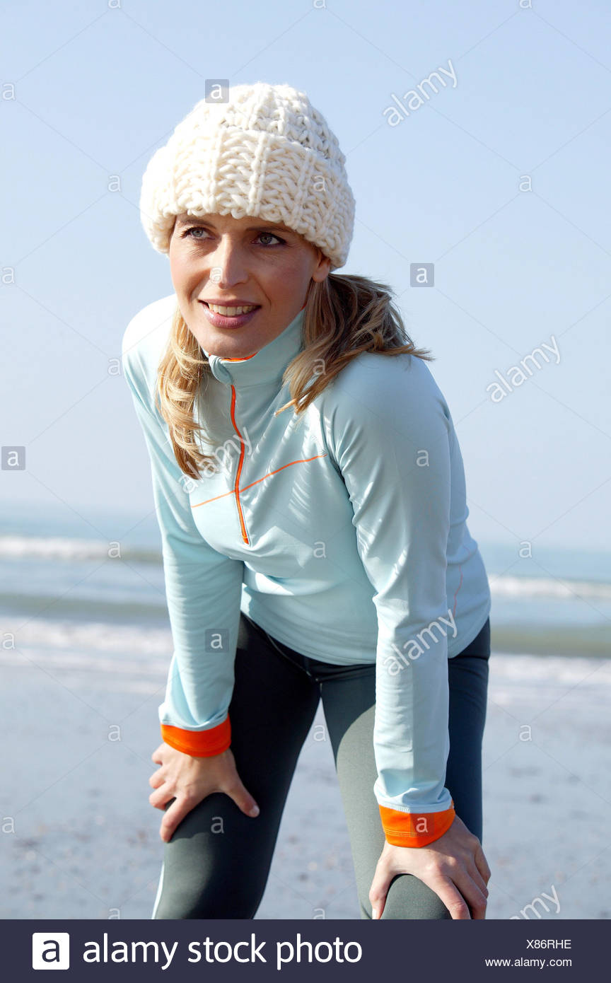 Beach, jogger, rest, autumn 30-40 years, winter clothes, cap, cord cap, woman, jogging, jog, running, fitness, training, activity, sportily, sport, mass sport, health, breathe deeply, rest, recover, exhale, depletion, conscious of body, conscious of health, sandy beach, sea, autumn, winter - Stock Image
