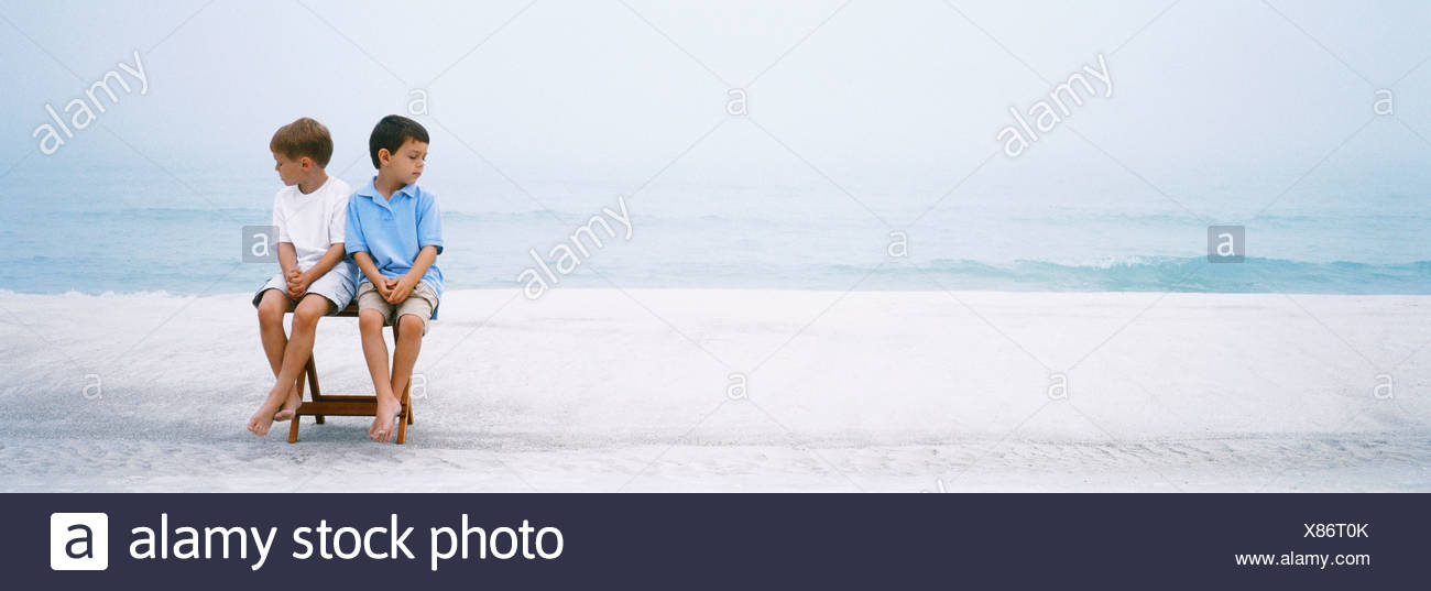 Two boys sitting side by side on folding chair at beach ignoring one another - Stock Image