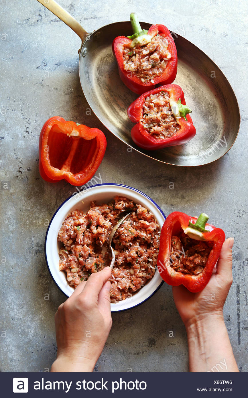 Female stuffing red peppers with mince meat.Top view - Stock Image