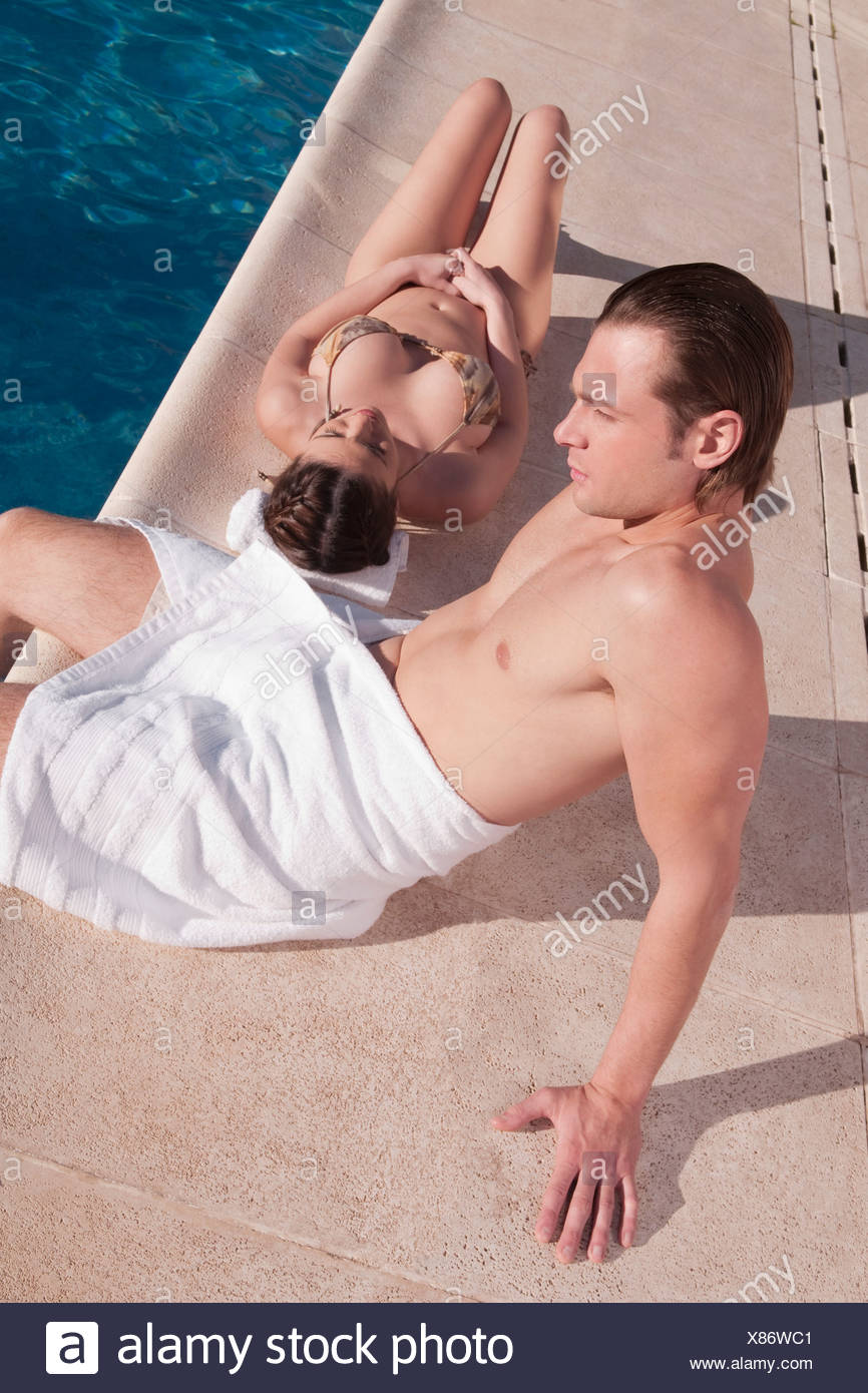 Couple resting by a swimming pool - Stock Image