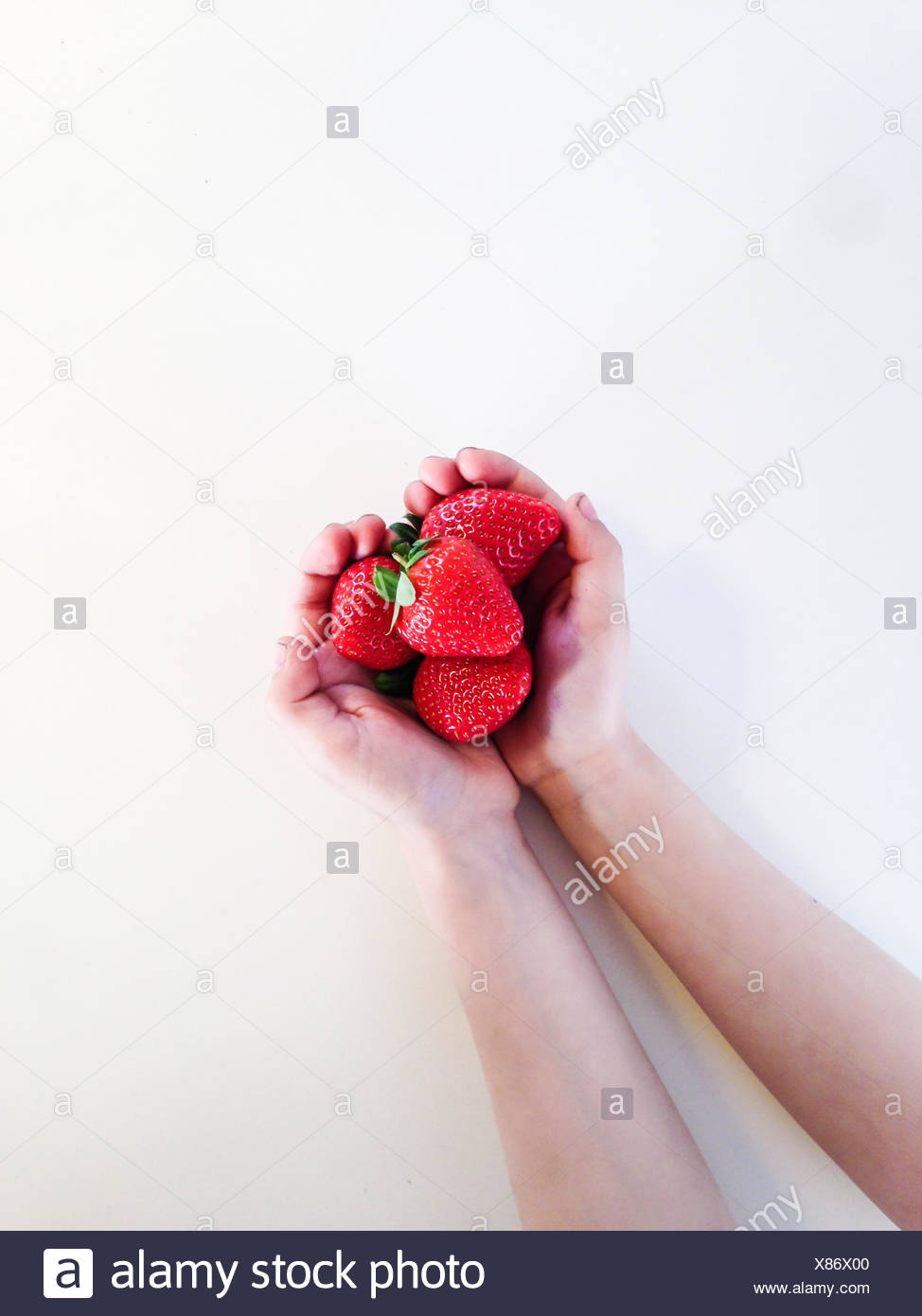 Boy with a handful of strawberries - Stock Image