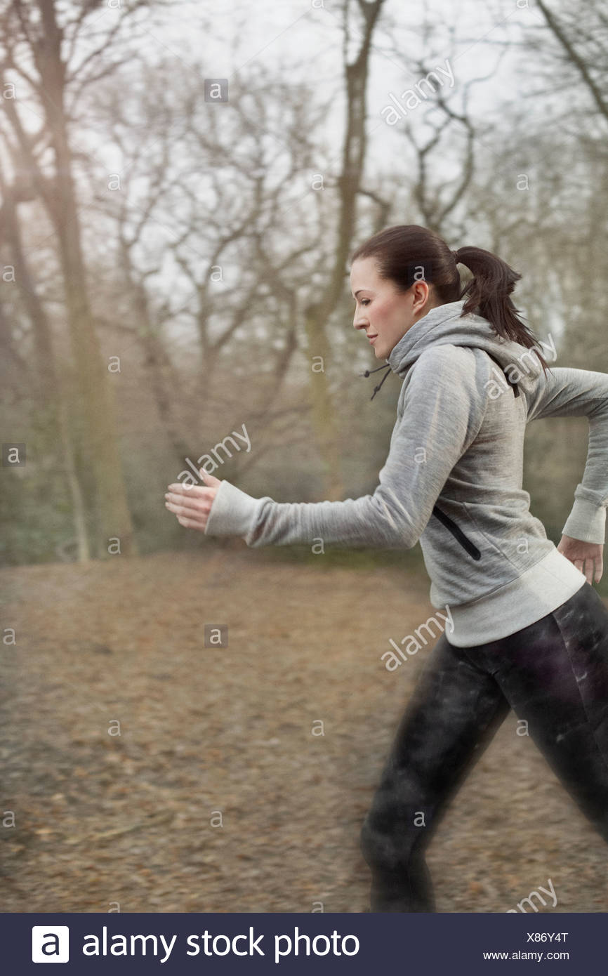 Young woman running through forest - Stock Image