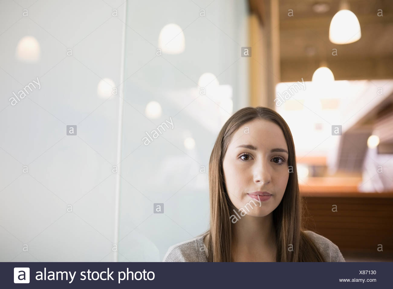 Portrait serious businesswoman leaning on frosted glass - Stock Image