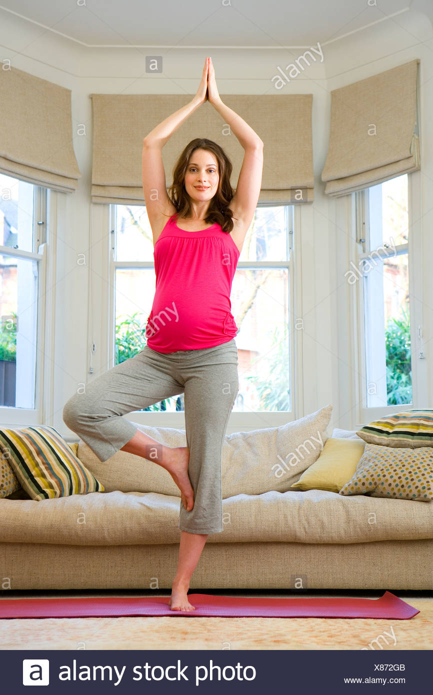 Young pregnant woman in tree pose yoga stance in living room, portrait - Stock Image