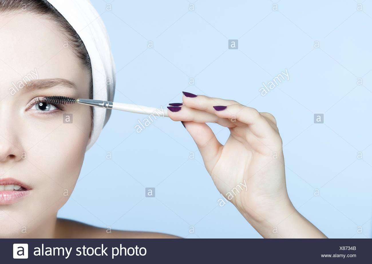 Portrait young blond woman making up eyelashes - Stock Image