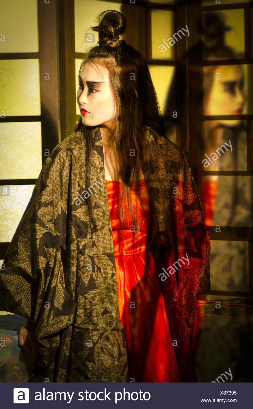 Beautiful young Japanese woman wearing red dress and kimono with reflection. - Stock Image
