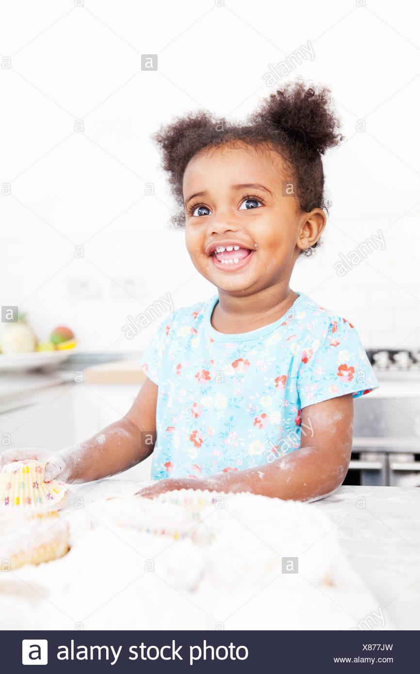Smiling girl baking in kitchen - Stock Image