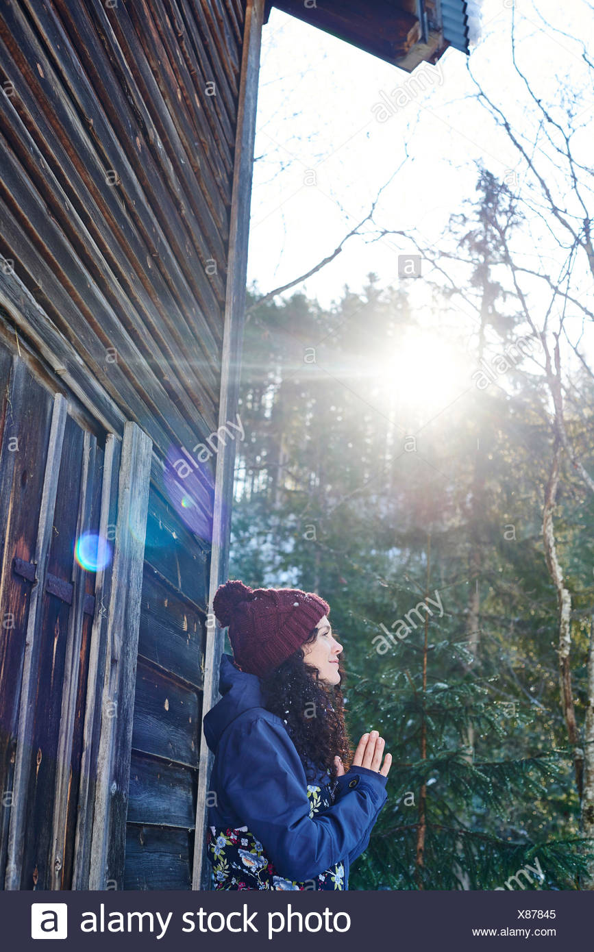 Woman in knit hat practicing yoga, meditating by log cabin - Stock Image