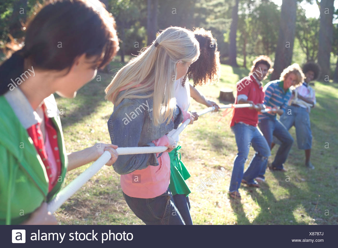 Men verses women vying for control of a rope - Stock Image