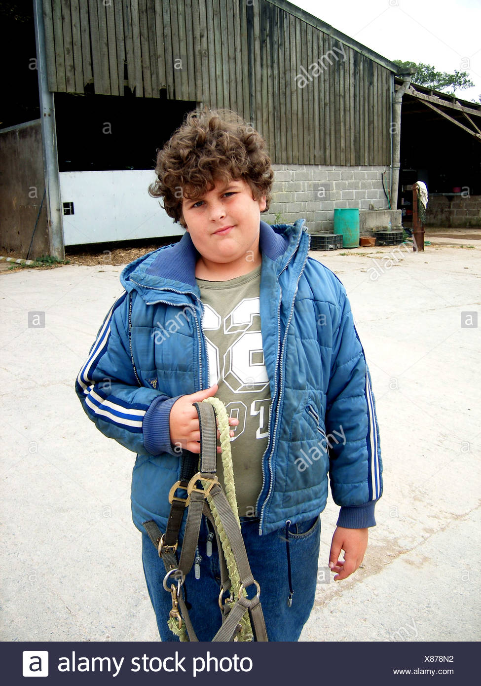 A brown curly haired male, wearing blue jeans, a khaki top and blue quilted jacket, holding a horse's bridle Caroline Bettaney - Stock Image
