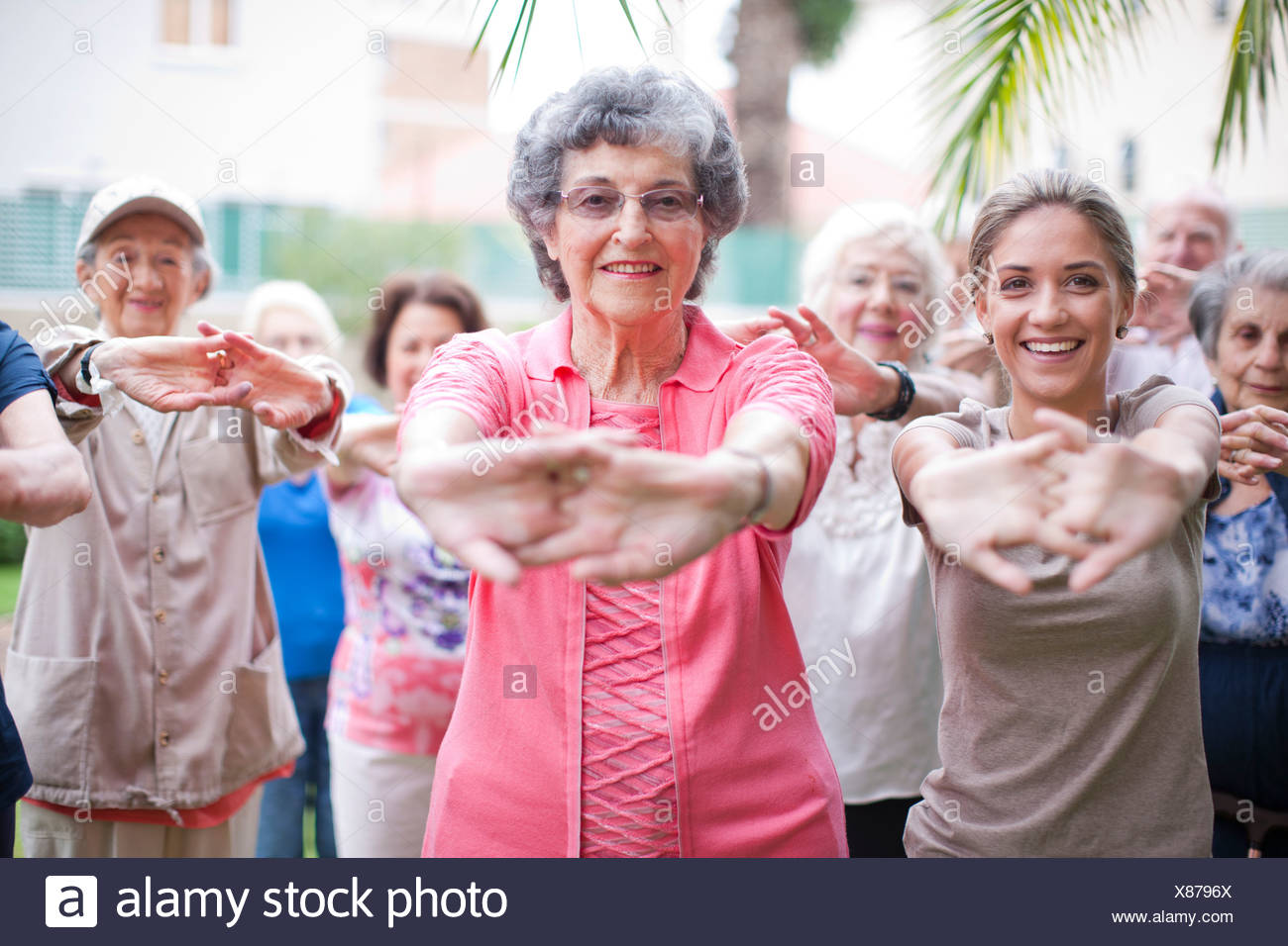 Medium group of seniors exercising in retirement villa garden Stock Photo