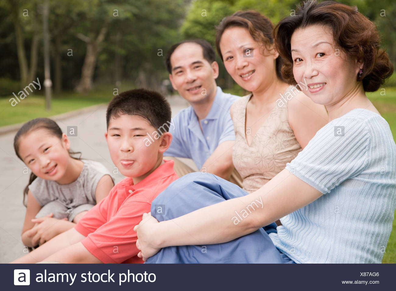 Portrait of a three generation family sitting together in a garden - Stock Image