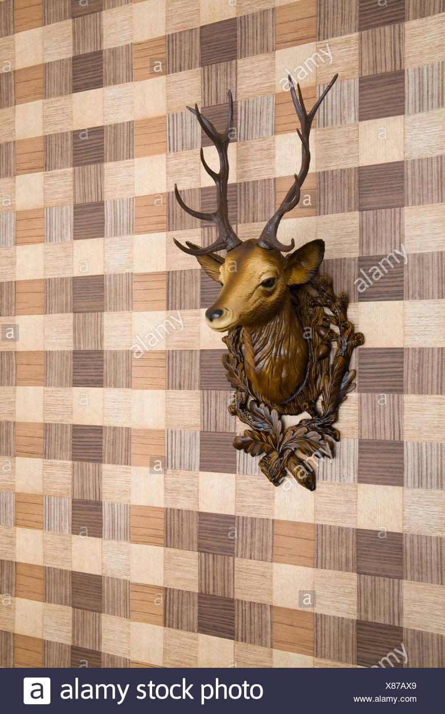 Plastic deer head mounted on imitation wood wallpaper, side view Stock Photo