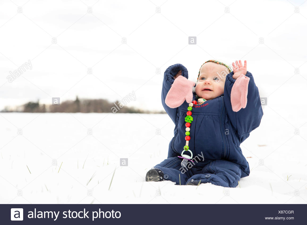 Baby, 9 months, sitting with a snowsuit in the snow - Stock Image