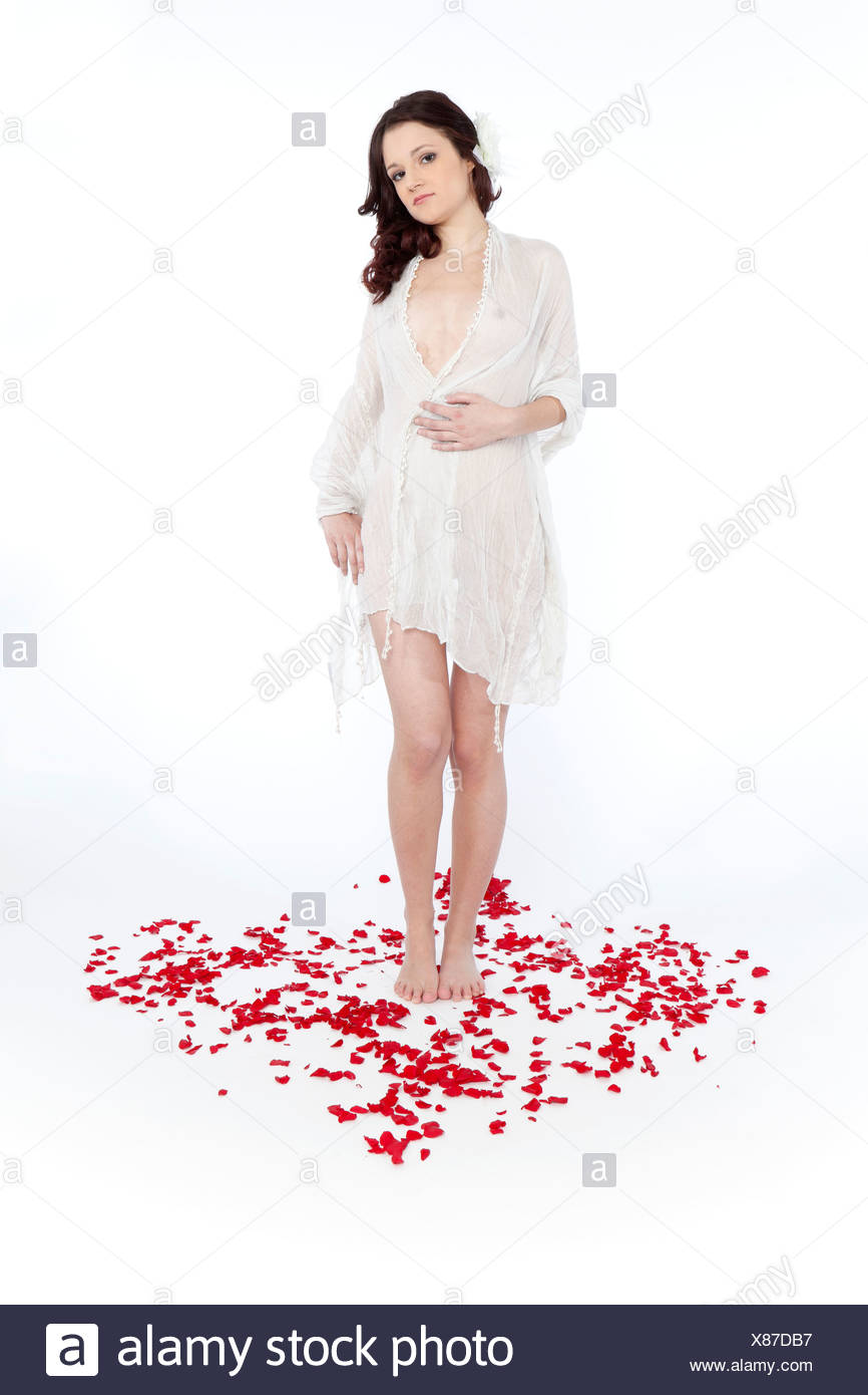 Young woman wearing a white transparent nightgown, standing on rose petals, shaped like a heart - Stock Image
