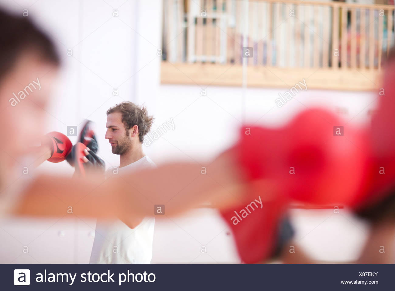 Young man and trainer boxing in gym - Stock Image