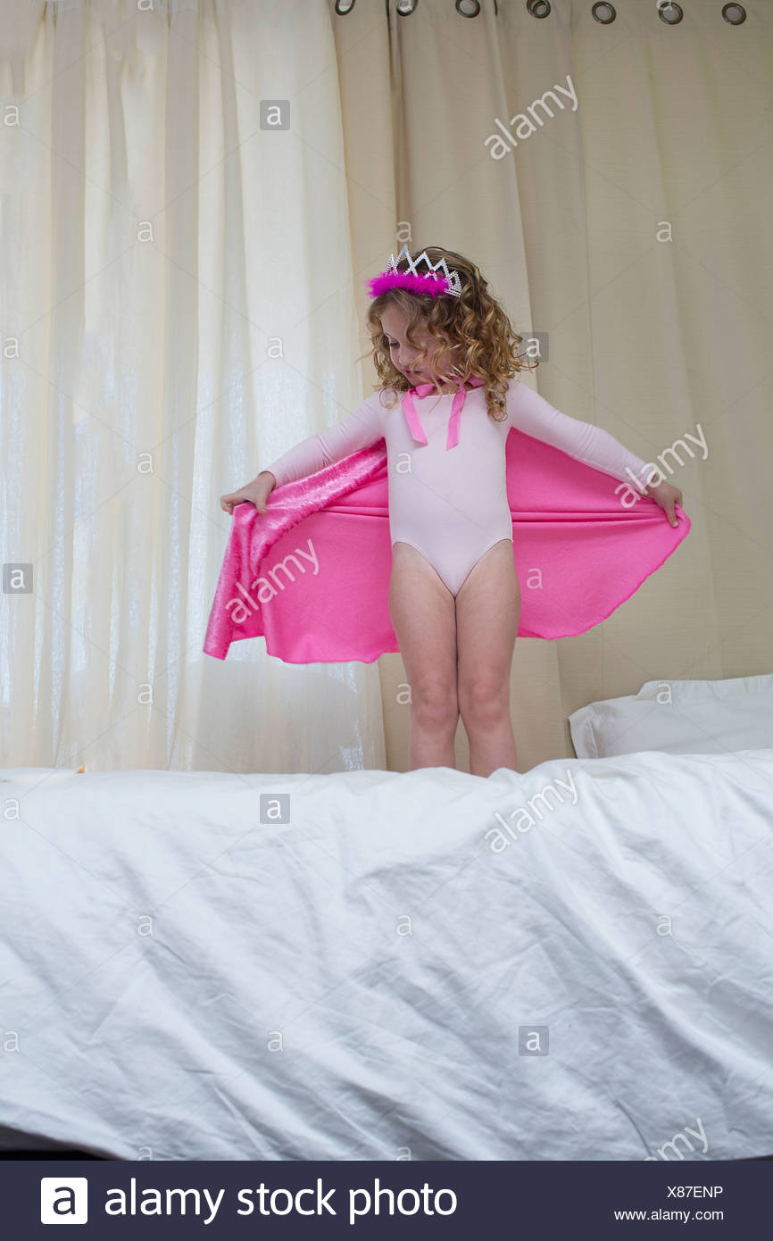 Young girl dressed up as a princess standing on bed - Stock Image