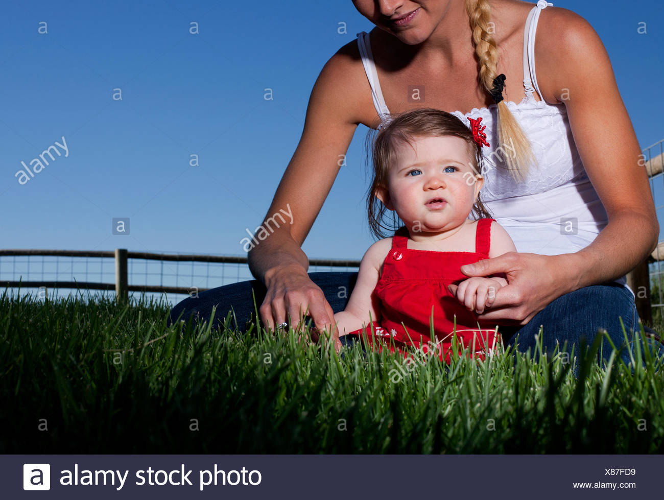 Portrait of mid adult woman sitting on grass with toddler daughter - Stock Image