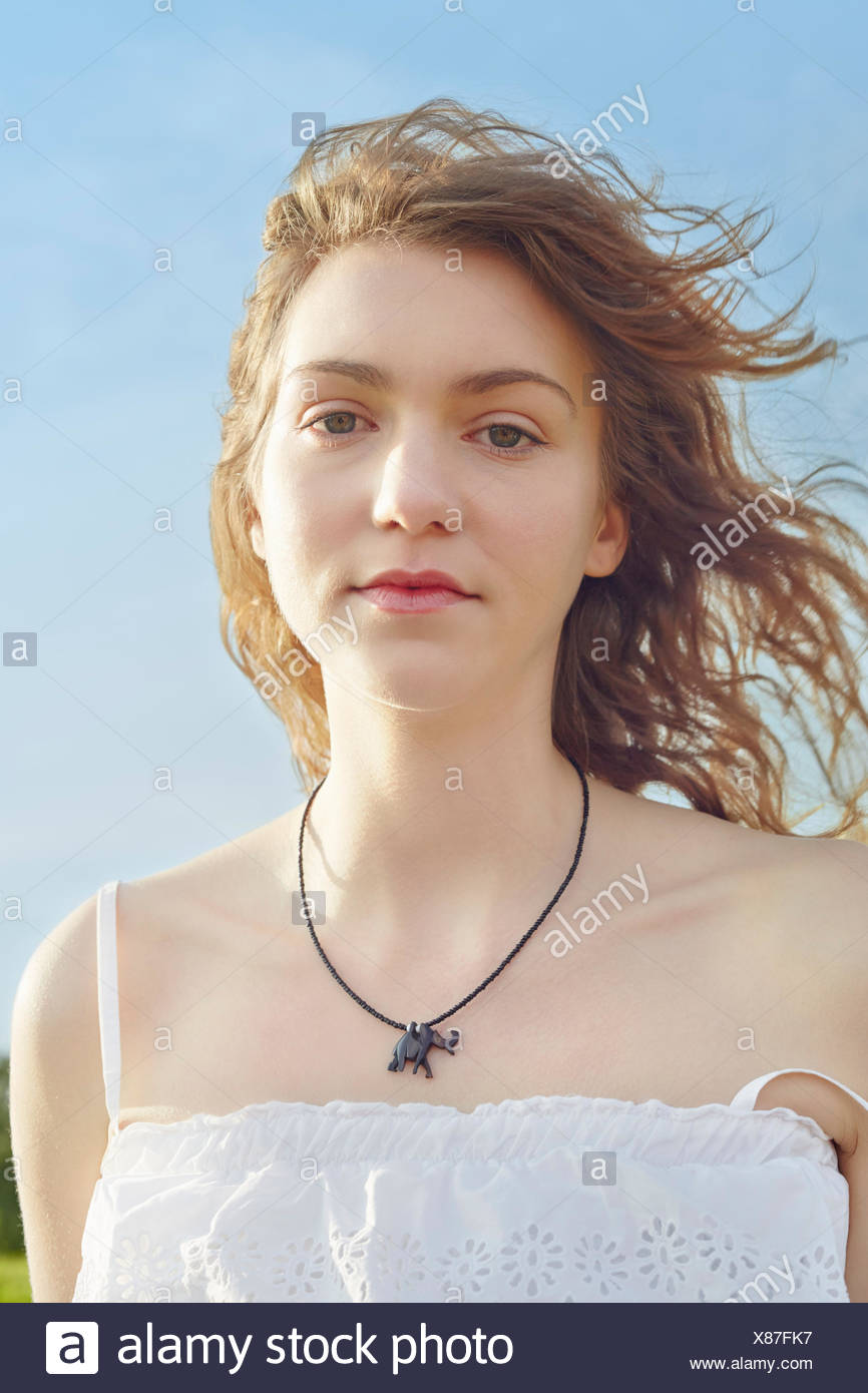 Portrait of serene young woman with hair blowing in breeze - Stock Image