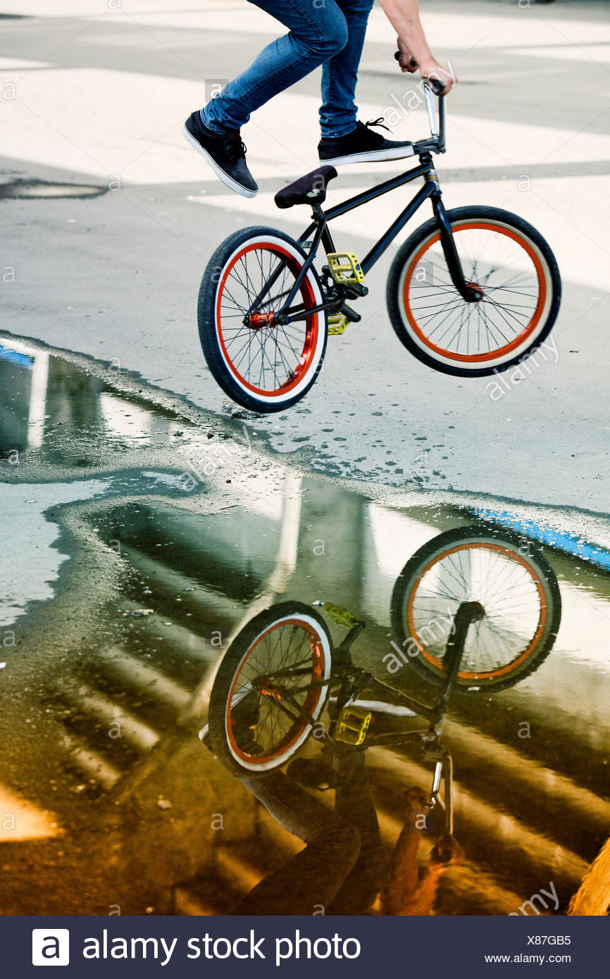 Reflections in a puddle of BMX biker performing a stunt - Stock Image