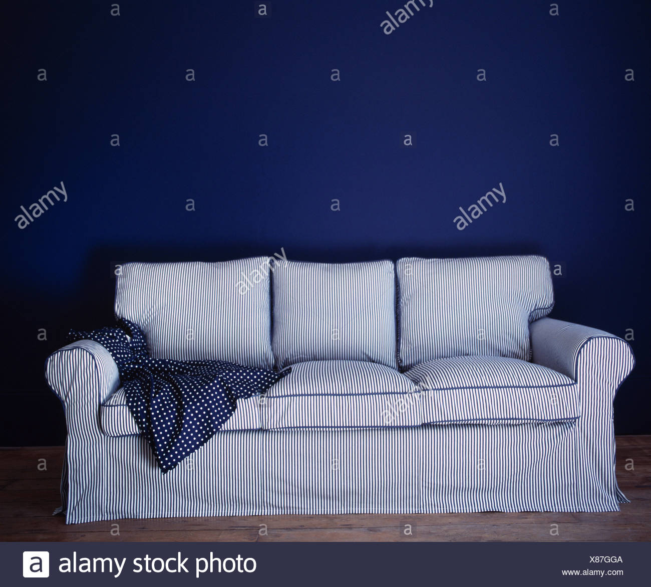 Close-up of traditional sofa with fine-striped loose-cover - Stock Image