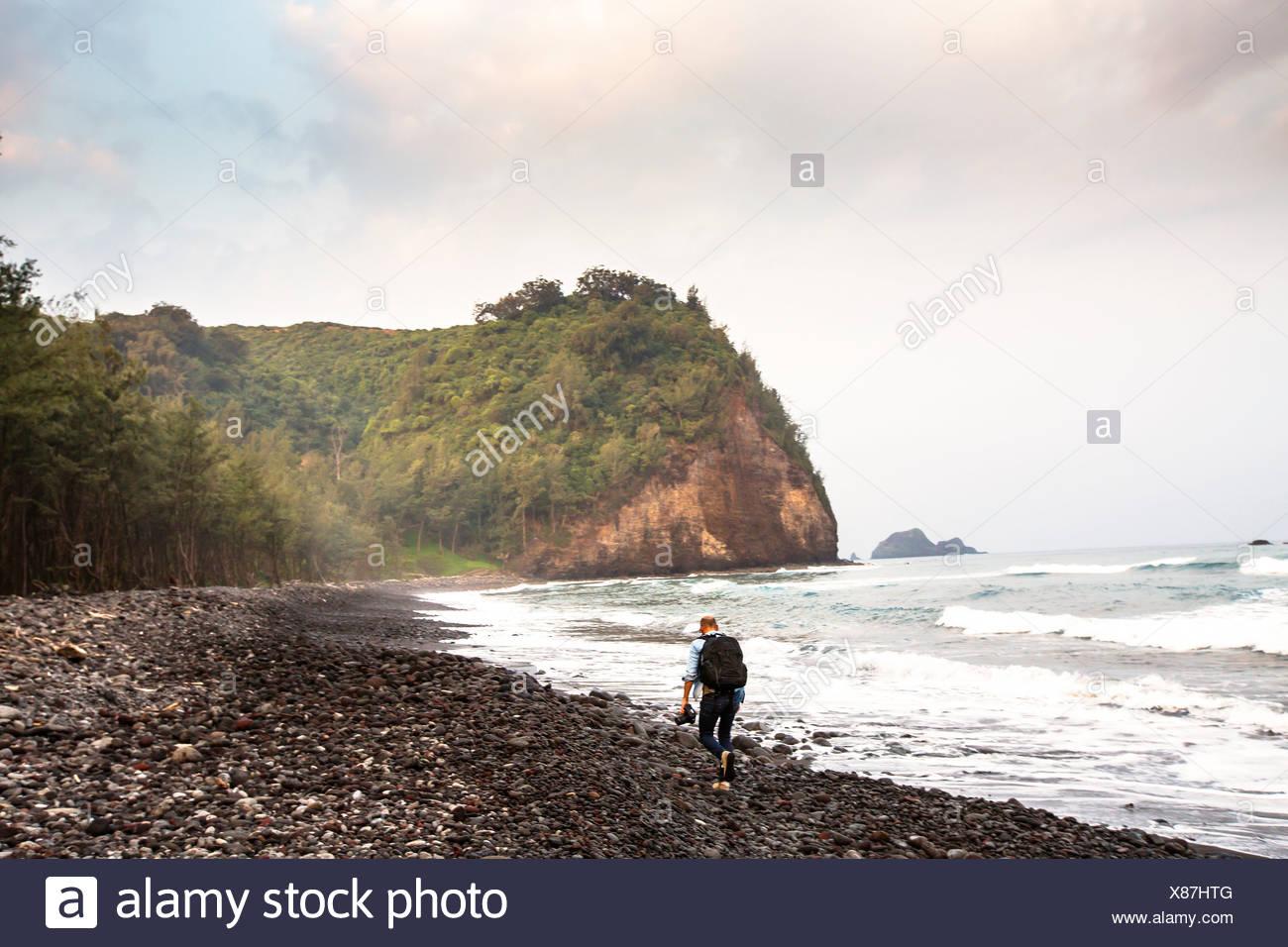 Mid adult man hiking along beach - Stock Image