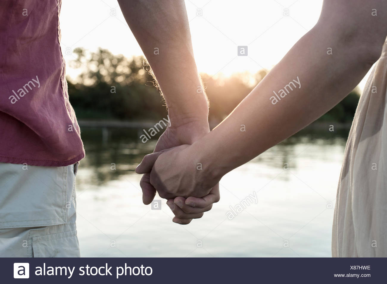 Mid section view of a couple in love holding hands during sunset, Bavaria, Germany - Stock Image