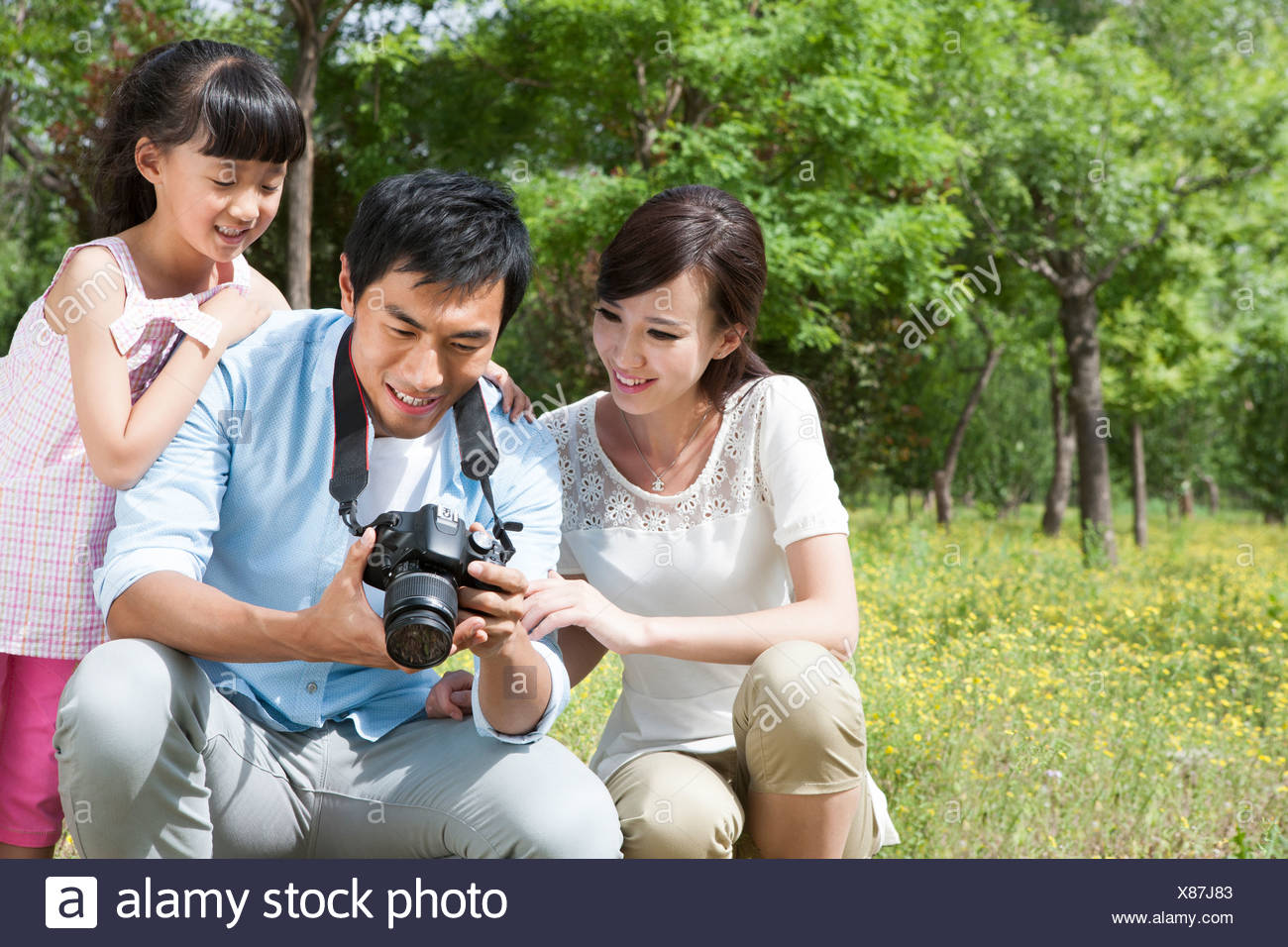 Happy family checking photos in SLR camera - Stock Image