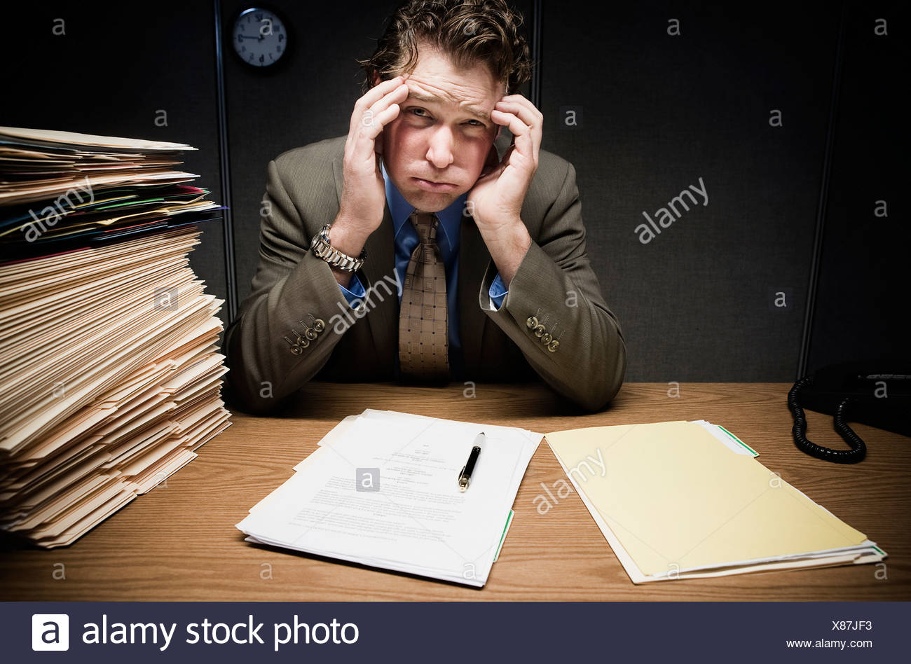 Stressed man at desk with paperwork - Stock Image