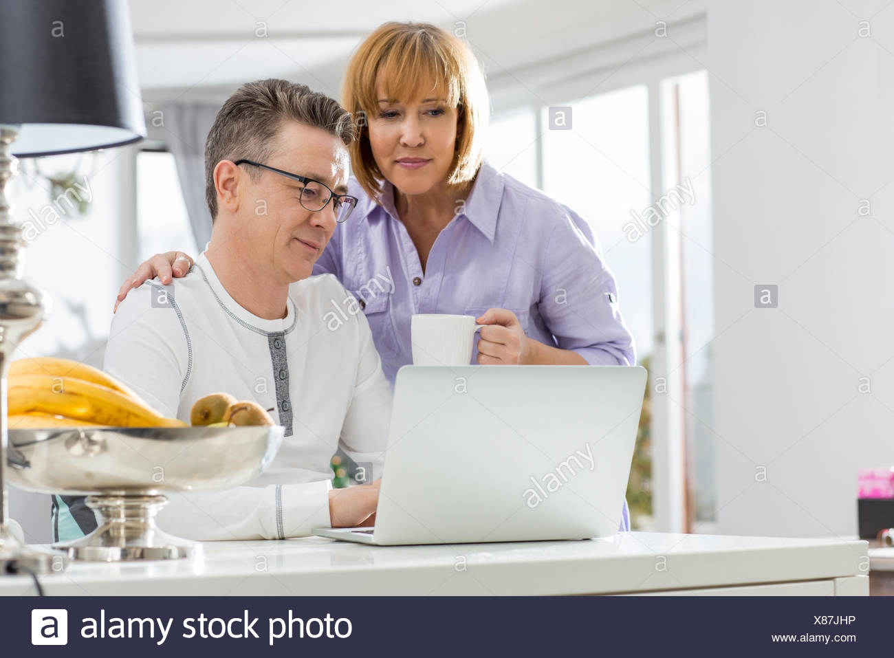 Mature couple using laptop together at table in house Stock Photo