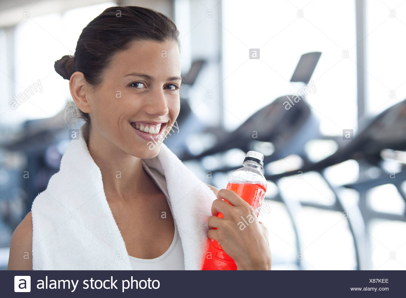 Woman hydrating after working out - Stock Image