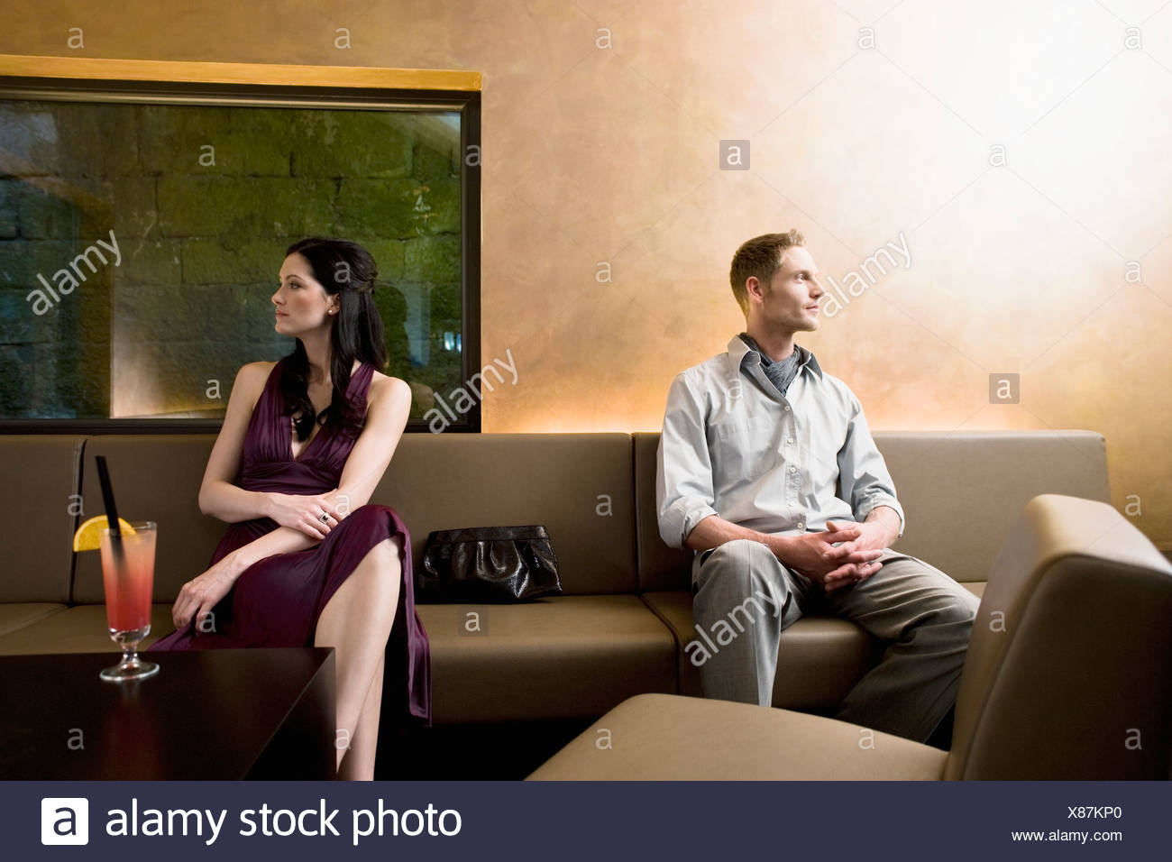 young couple sitting in bar looking away from each other - Stock Image