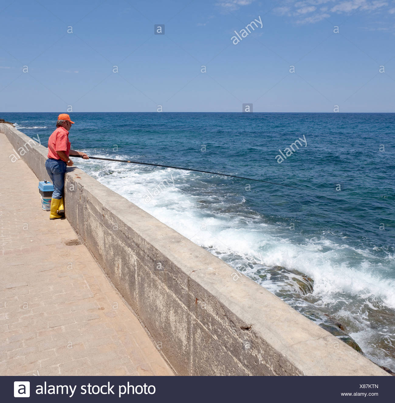 A fisherman on the quay of Kyrenia, also known as Girne, Northern Cyprus, Cyprus, Europe - Stock Image