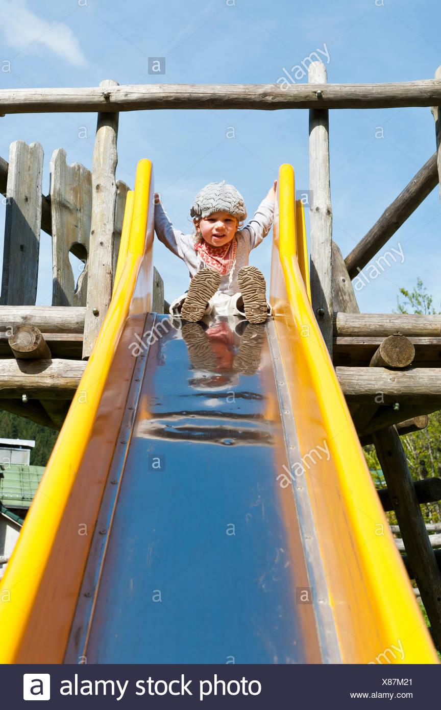 Little girl sitting on top of a slide, Bavaria, Germany - Stock Image