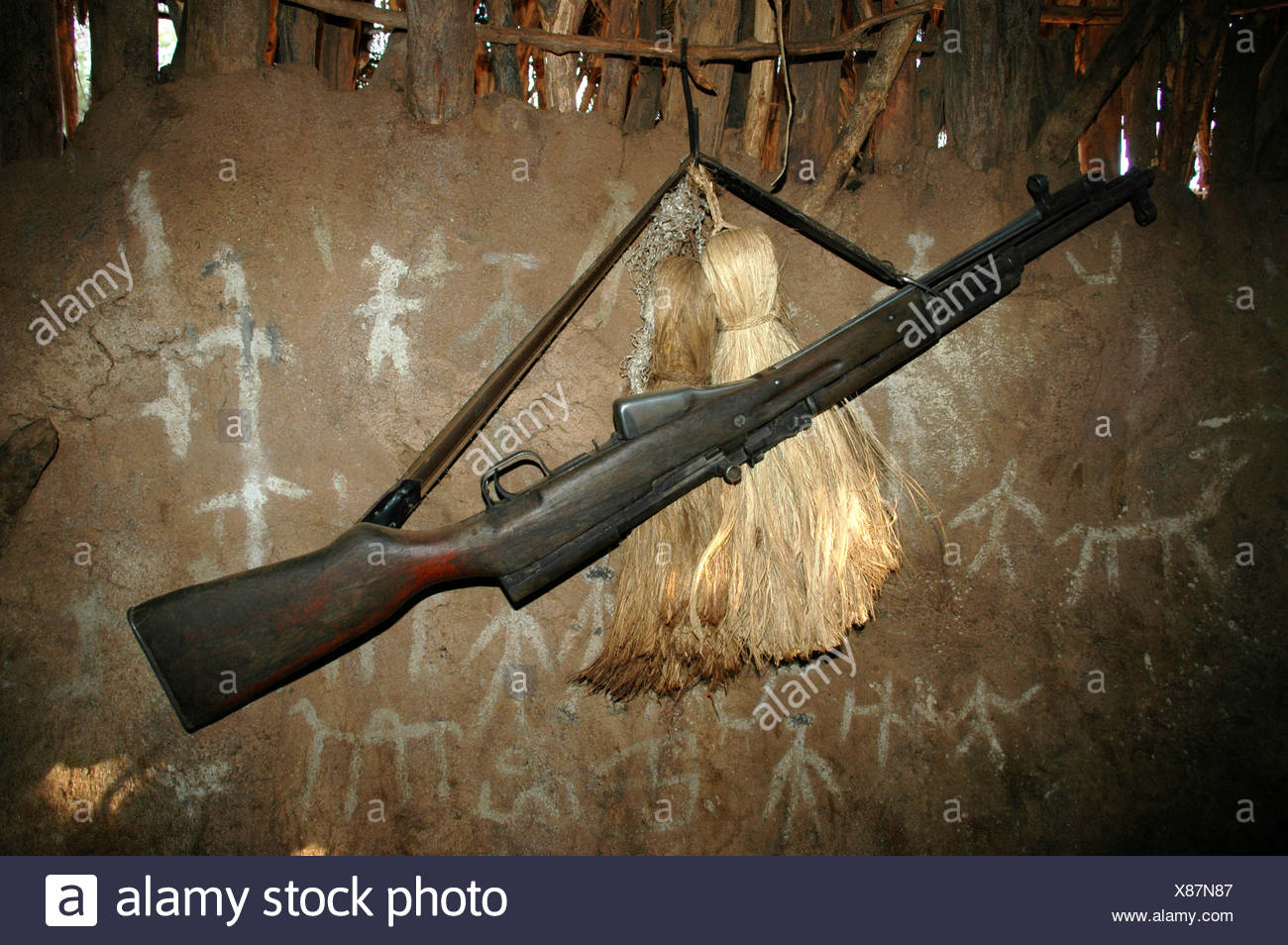 Gun, carbine hanging on the wall of a clay hut, Turmi, Ethiopia, Africa - Stock Image